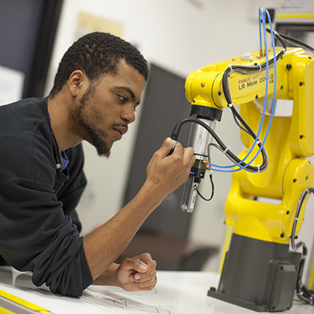 Student working with an industrial robot